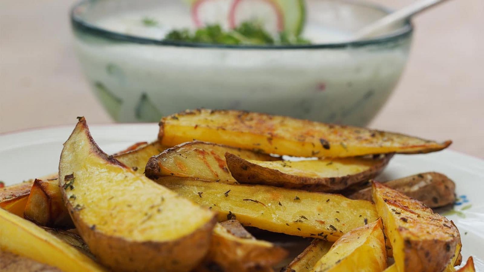 Würzig-knusprige Kartoffelwedges mit einem leichten veganen Joghurt-Gurkendip und frischen Gartenkräutern