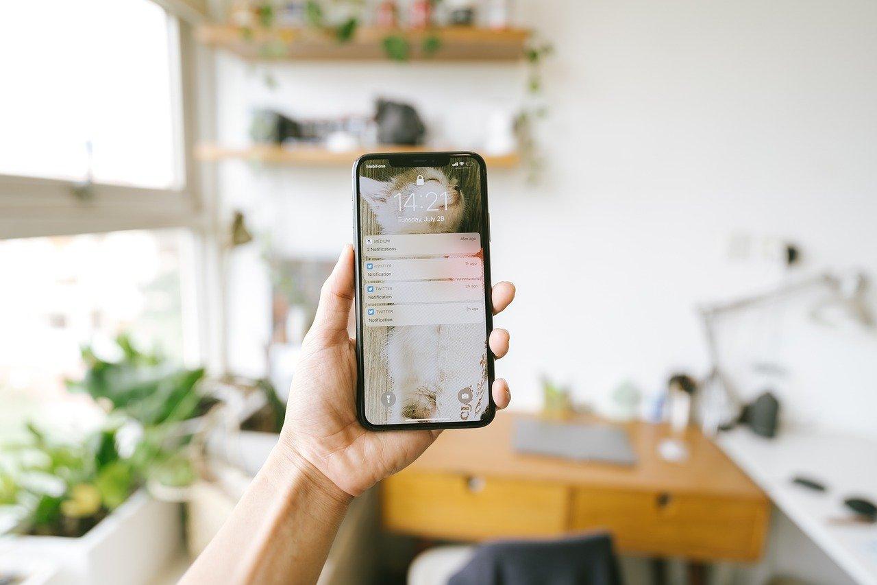 Wenn Social Media nicht mehr guttut. Eine Hand hält in einem Arbeitszimmer ein Smartphone in die Höhe. Auf dem Bildschirm werden verschiedene Twitter-Notifications angezeigt.
