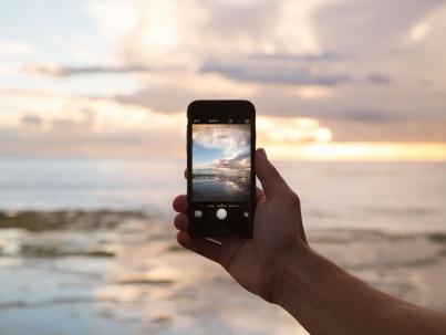 Wenn Social Media nicht mehr guttut. Eine Hand hält ein Smartphone mit geöffneter Kamera-App am Strand. Im Display sieht man einen Ausschnitt des Sonnenuntergangs am Meer.